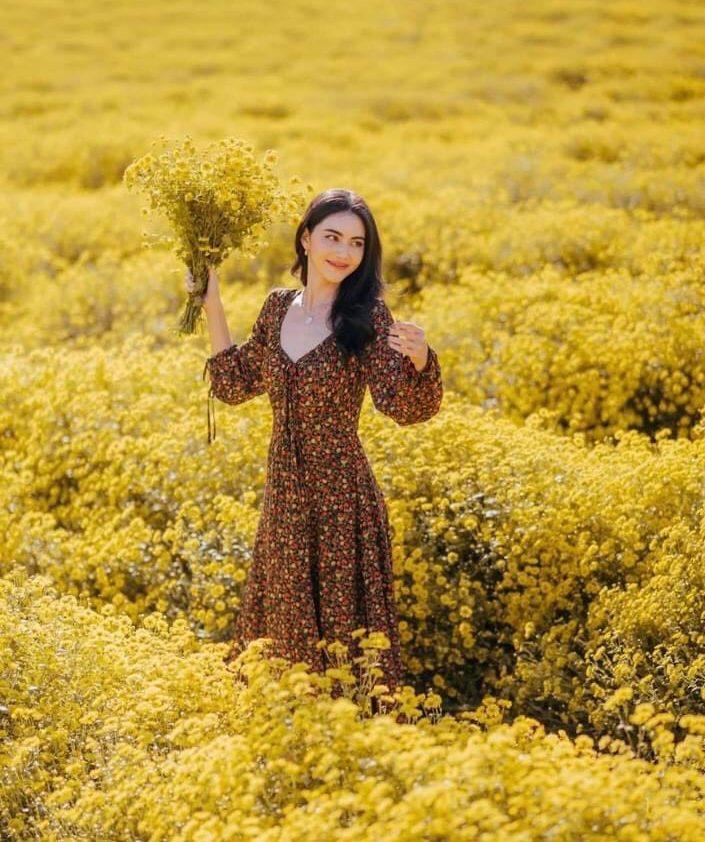 ถ่ายรูปกับทุ่งดอกไม้หยิบดอกไม้มาถือยิ้มแบบไม่มองกล้อง