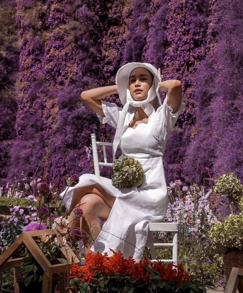 ถ่ายรูปกับทุ่งดอกไม้จัดท่านั่งสวยๆยืดอกแล้วมองมาที่กล้องยิ้มเบาๆ