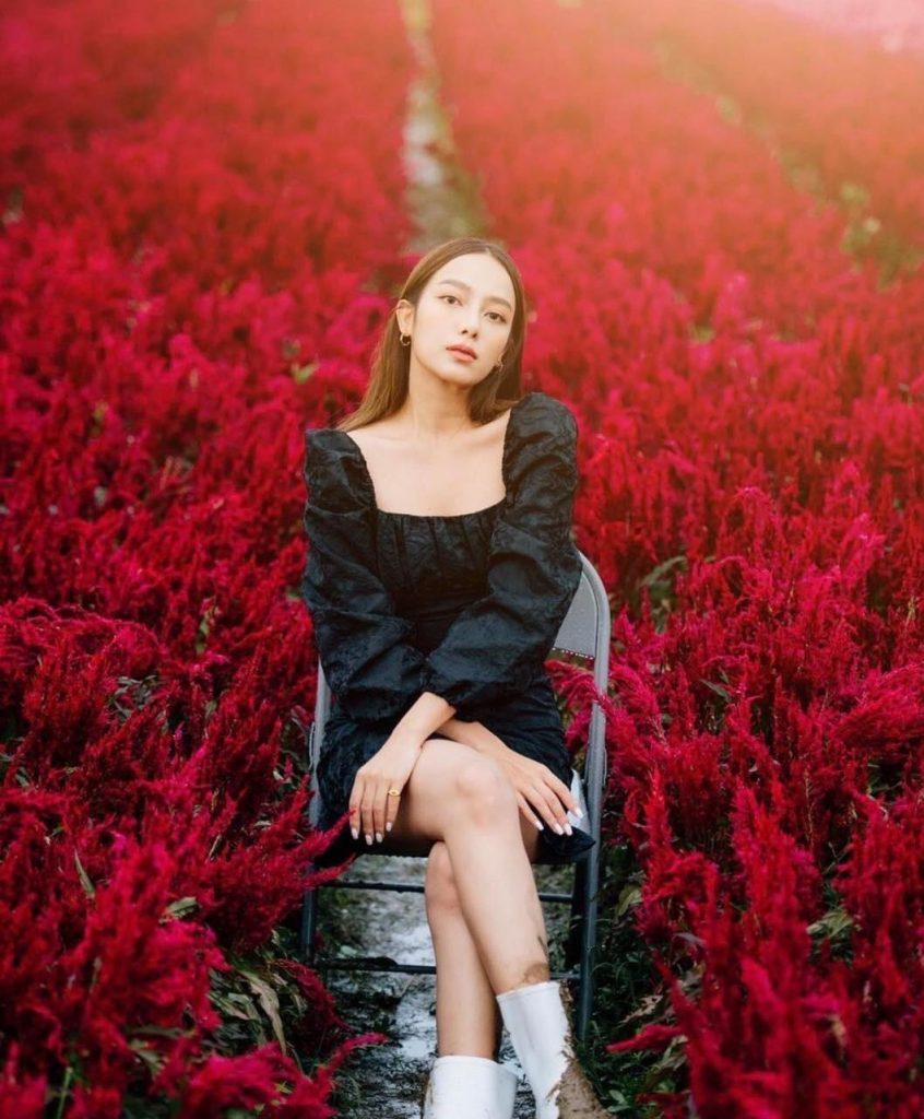 ถ่ายรูปกับทุ่งดอกไม้นั่งสวยๆมองกล้องแบบมั่นใจ