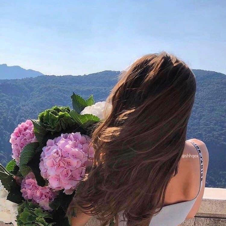 ถ่ายรูปกับช่อดอกไม้บนเขาแบบหันหลังโชว์ดอกไม้ไว้ข้างๆตัวเอง